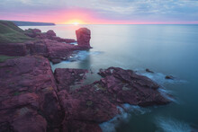 Coastal Landscape Of The Deil's Heid (Devil's Head) Red Sandstone Sea Stack At Seaton Cliffs During A Colourful Sunset Or Sunrise At Arbroath East Coast Of Angus, Scotland.