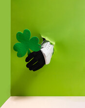 Storm Trooper Hand Is Holding Green Clover From Bright Green Wall Background.