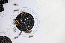Many Bullets On Shooting Targets On White Table In Shooting Range Polygon. Training For Aiming And Shooting
