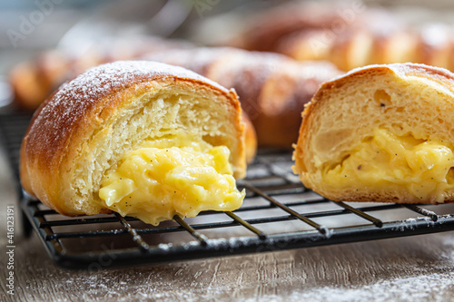 Homemade fresh yeast buns with custard filling with powdered sugar on black metal grille Fototapeta