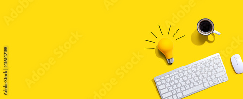 Fototapeta Computer keyboard with a yellow light bulb from above obraz