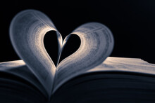 Close Up Heart Shape From Paper Book On Dark Background. Lights And Shadows Concept. Black And White Photography
