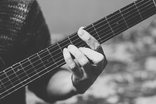 Black And White Photo Of A Musician Playing The Guitar. Fingers On A Guitar Fretboard Close Up