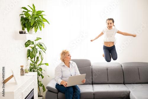 Fototapeta Portrait of grandmother and granddaughter shopping online together at home obraz