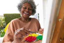 African American Senior Woman Smiling While Painting On Canvas Standing On Porch Of The House