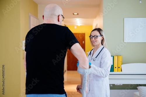 Smiling caring young female nurse doctor caretaker assisting patient in rehabilitation recovery at medical checkup visit. © Daniel Jędzura