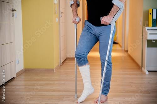 Disabled young man using crutches to walk. Rehabilitation of a broken leg at home. © Daniel Jędzura