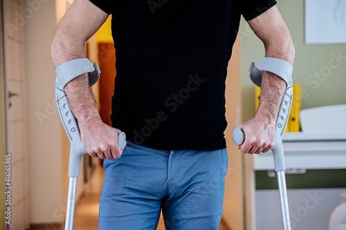 Close-up mid section of a man with crutches. Rehabilitation of a broken leg at home. © Daniel Jędzura