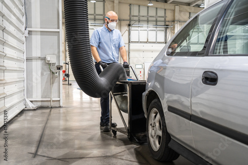 Fototapeta A technician placing a smoke absorber prior to an emission control of a periodic