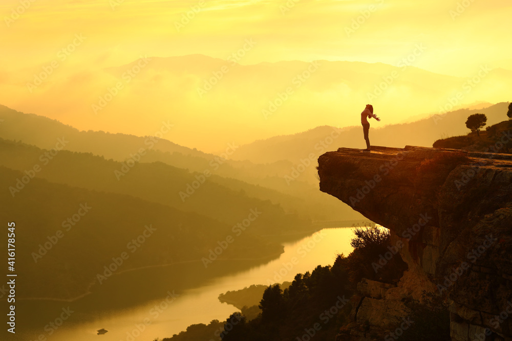 Fototapeta Woman silhouette breathing fresh air in the top of a cliff