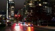Cars stopping for a red traffic light waiting till it changed to green and proceed there trip over an intersection in downtown Vancouver between skyscrapers. Timelapse by night