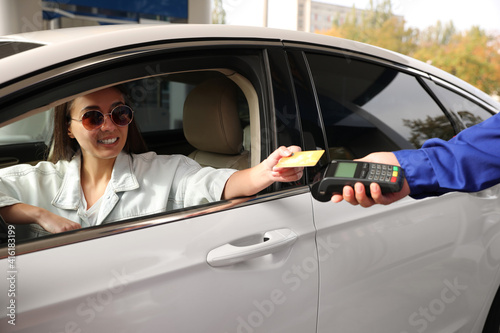 Fototapeta Woman sitting in car and paying with credit card at gas station obraz