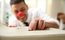 Man With Clown Nose Putting Pins Onto Colleague's Chair In Office, Focus On Hand. Funny Joke