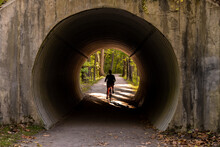 Woman Bikes Through Tunnel On Towpath
