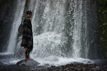 A Portrait Of An Asian Man Wearing A Lombok-Indonesian Songket Cloth Enjoying The Freshness Of A Waterfall In The Middle Of The Forest. A Traveler Relaxing And Bathing Under A Swift Waterfall