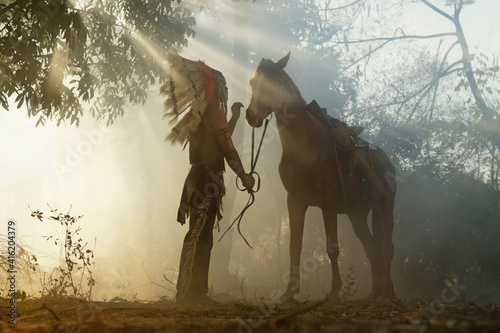 Stampa su Tela The Indians are riding a horse and spear ready to use In light of the Silhouette, American Indian warrior, chief of the tribe