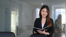 Confident Young Businesswoman In Suit Holding Folder And Smiling To Camera.