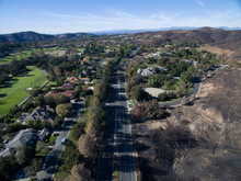 Lush Golf Course Across The Road From A Wildfire Charred Hillside