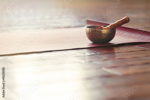 Fotografie, Obraz A singing bowl stands on a yoga mat on a wooden floor with copy space