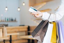 Main Avec Des Sacs En Papier Et Une Carte De Crédit