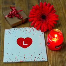 Composition With Gift Box And Book With Heart-shaped Cover And Letter L Highlighted On Red Background And Red Flower