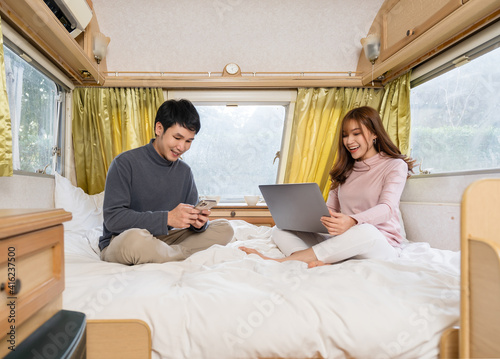 Fotografia, Obraz couple using smartphone and laptop computer on bed of a camper RV van motorhome