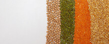 A Mixture Of Cereals Chickpeas, Peas, Lentils, Mash, Buckwheat Laid Out In A Row On A White Background Close-up