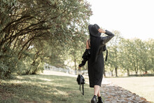 Fashion Young Woman In Black Vintage Dress In Beautiful Stylish Hat In Leather Trendy Jacket In Boots With Bag Walks In Park Near Trees At Sunset. Lovely Girl In Elegant Black Wear Enjoy In Sunny Day.