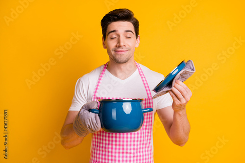 Fototapeta Photo portrait of man in kitchen gloves opening pot smelling food inside isolated on vivid yellow colored background obraz