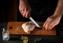 Cooking A Chicken Leg With The Hands Of A Chef On A Dark Background. Cut The Chicken Meat With A Knife. Free Advertising Space For A Restaurant