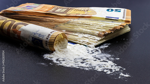Bundle of euro banknotes and drugs heroin or cocaine on a black background Fototapet