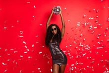 Photo Of Young Excited African Girl Happy Positive Smile Have Fun Disco Ball Club Fly Air Serpentine Isolated Over Red Color Background