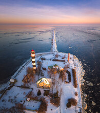 Lighthouse At Colorful Sunrise At Seaside In Frosty Winter Morning. Snowy Breakwater Leading Into Frozen Sea.