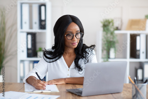 Happy black young business lady working on laptop at office, taking notes during Poster Mural XXL