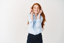 Dreamy Smiling Redhead Woman Making A Wish, Expecting Good News With Closed Eyes And Crossed Fingers, Standing Over White Background