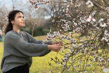 Attractive Young Lady Happy Enjoying The Blossoms Of The Almond Tree In Spring. Blooming Flowers Springtime.