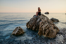 Girl In Black Dress Posing At Sunset On The Rock At Sea