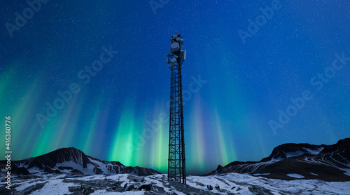 Fotografie, Obraz Telecommunication tower with 5G cellular network antenna on night winter landsca