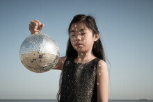 Young Girl In Silver Dress Holding A Disco Ball Reflecting Light Patches Outside Under A Blue Sky