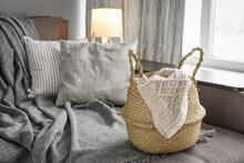 Straw Wicker Basket With Knitting On Sofa