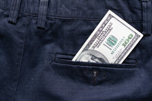 One Hundred American Dollars Banknote In A Jeans Pocket On Rotating Table. Extreme Close-up, Shallow Depth Of Field. Business
