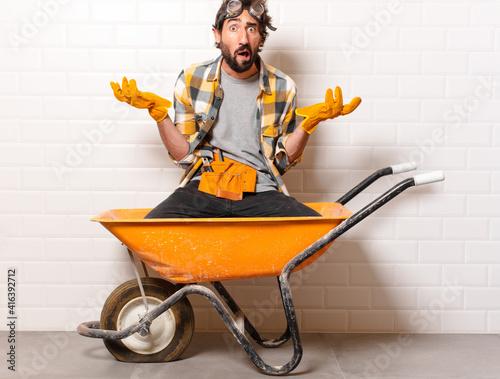Obraz na plátne young bearded construction worker man on a wheelbarrow