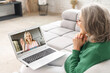 canvas print picture - Back view on the laptop screen with a video call participant on it, two middle-aged women have a video meeting on the laptop. Senior lady talks online with an adult daughter, mid-age friend, coworker