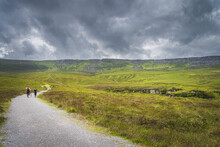 People Hiking On A Trail Between Green Hills And Peat Bog Leading To Cuilcagh Mountain With Stormy, Dramatic Sky In Background, Northern Ireland