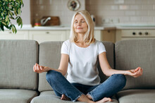 Calm Attractive Middle Aged Woman Sits On Sofa At Home And Chilling. Senior Female Is Practise Yoga And Meditation In Lotus Position With Eyes Closed, Relieve Stress, Calmness Concept