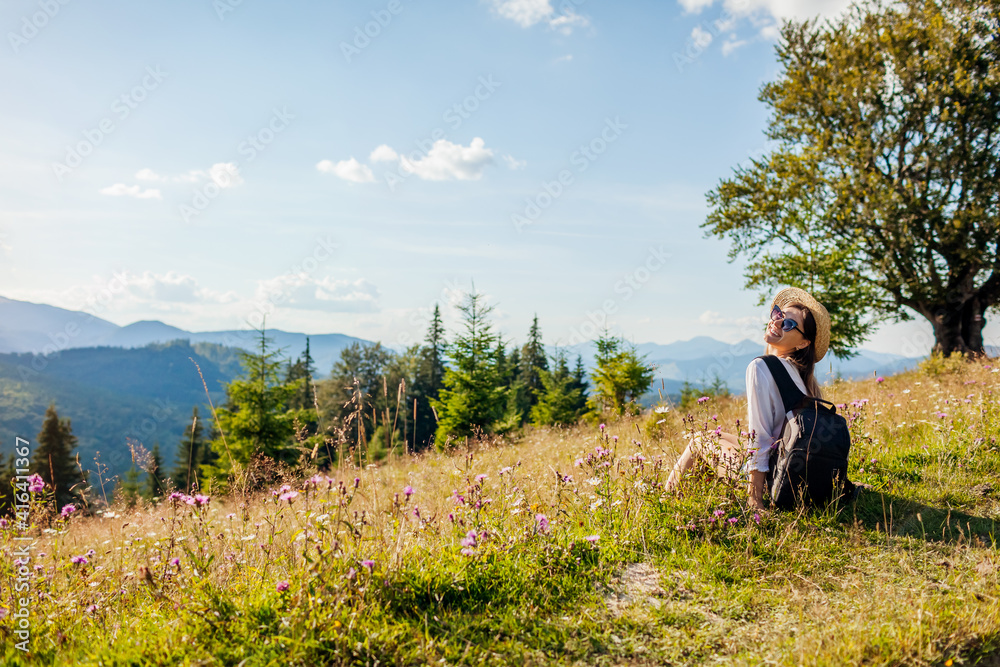 Fototapeta Traveling in summer Ukraine. Trip to Carpathian mountains. Happy woman tourist sitting in flowers after hiking