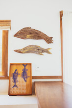 Modern Luxury Summer Holiday Or Vacation Beach House Interior Decoration. Rustic Wooden Statues Of Fish On The White Wall And A Wood Plaque With Two Fish Printed On It. Copy Space For Text