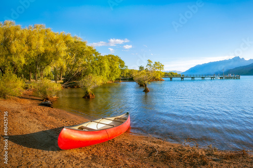 A red canoe on the shore of Lake Wakatipu at Glenorchy Wharf at golden hour in New Zealand, South Island Fototapeta