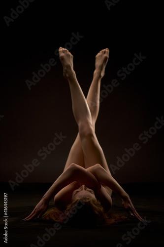 Obraz Naked woman lying on floor in dark studio - fototapety do salonu