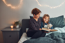 Mother Reading Book Her Daughter In Bed Before Going To Sleep. Reading Stories Before Sleep. Bedtime Stories For Child